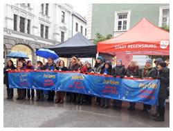 """Foto: Infostand und Frauen mit Plakaten """"frei leben ohne gewalt"""" in verschiedenen Sprachen"""