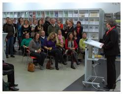 Foto: Frau beim Vortrag, interessierte ZuhörerInnen